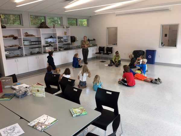 Children captivated by staff during programming in the Nature Center.